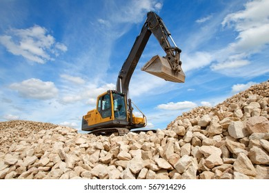 Excavator unload gravel. The stones for the road. Unloading stone. Excavator bucket. The quarry where the stone is mined.