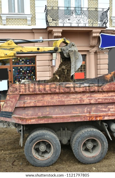 Excavator used to dig up tree-stumps and roots in the city. Loading of roots on  a dump truck