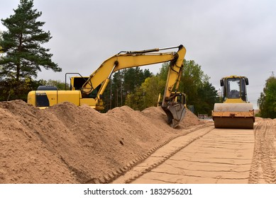Excavator and Vibro Roller Soil Compactor at road construction and bridge projects in forest area. Heavy machinery for road work. Building a road works. Leveling and compaction of ground
