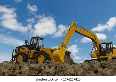 Excavator and Wheel loader are digging the soil in the construction site on the blue sky  background