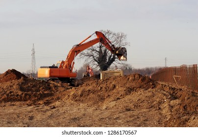 Excavator at work among dune of dirt in a new development area