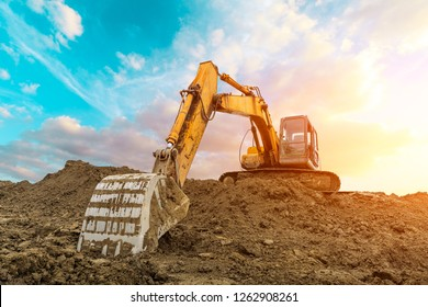 Excavator work on construction site at sunset