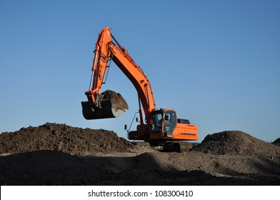 Excavator at work - Orange excavator at work in open sand mine and a blue sky