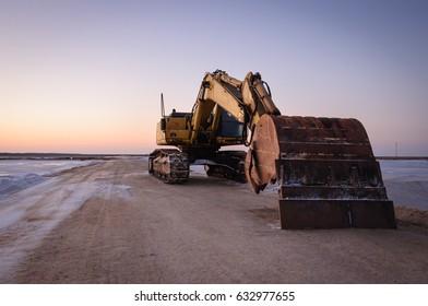 Excavator at work in salt works with sunset