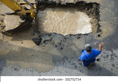 Excavator and worker repairing damaged water supply