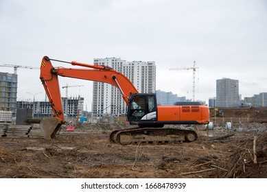 Excavator working at construction site on earthworks. Backhoe digs ground for the foundation and for paving out sewer line. Construction machinery for excavating, loading, lifting and hauling of cargo