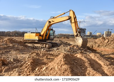 Excavator working at construction site on earthworks. Backhoe on road work digs ground. Paving out sewer line. Construction machinery for excavating foundation, loading, lifting and hauling of cargo