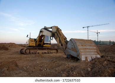 Excavator working at construction site on road work. Backhoe digs ground for the foundation and for paving out sewer line. Construction machinery for excavating, loading, lifting and hauling of cargo