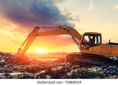 Excavator working at construction site on sunset