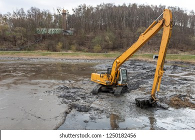 Excavator working at deepening the pond
