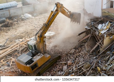 Excavator working at the demolition of an old  building house.