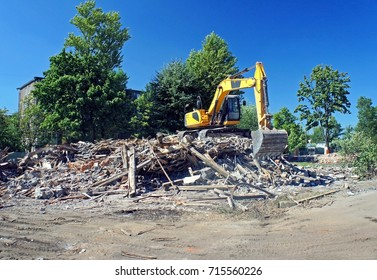 Excavator working at the demolition of an old house, yellow machine, construction site, sunny day