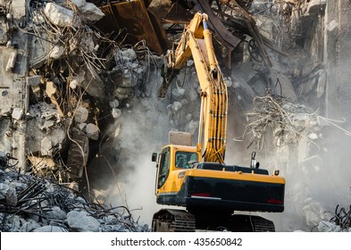 Excavator working at the demolition of an old industrial building.