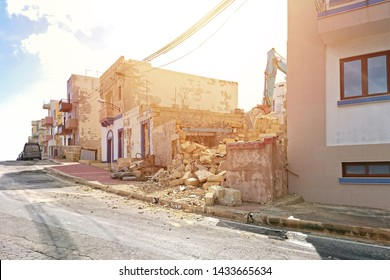Excavator working at the demolition of an old residential building among other houses. Maltese Excavation and demolition works concept old house with new rules