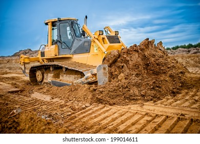 Excavator working with earth and sand in sandpit in highway construction site