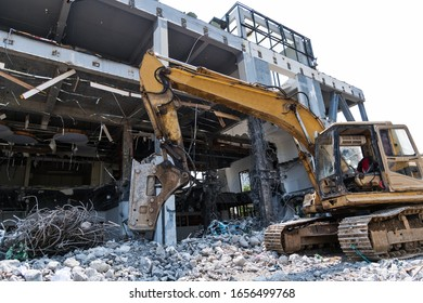 Excavator working on building demolition site.