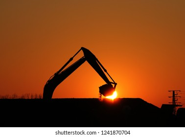excavator working on construction site scoop silhouette