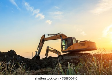 excavator working on construction site and sunrise landscape