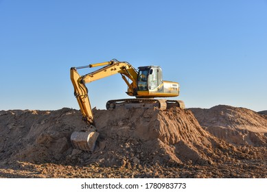 Excavator working on earthmoving at open pit mining. Yellow Backhoe digs sand and gravel in quarry. Heavy Construction Equipment Machines in Action. Digger during excavation at construction site.