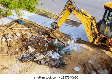 Excavator working on junk dump.Garbage the city. Soil pollution.