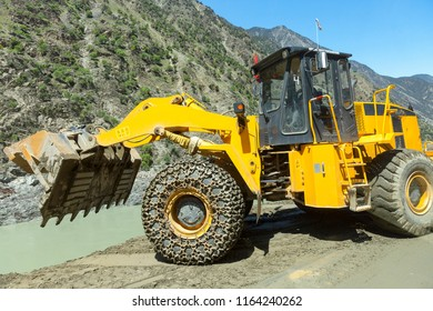 Excavator working on repairing a road ,heavy industry hydraullic with chain protect at front wheel ,new silk road National Highway 35 or China-Pakistan Friendship Highway.