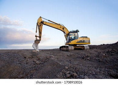 Excavator working at open pit mining on sunset background. Backhoe digs gravel in sand quarry on blue sky background. Recycling old asphalt at a landfill for the disposal of construction waste