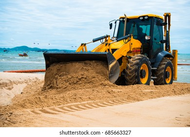 Excavator works to adjust the sand at the beach to smooth and beautiful sand