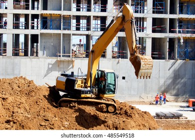 An excavator works in the construction of a house. Digging up the soil.
