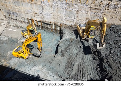 Excavators dig at a construction site of a street and a subway. Baggers transport dirt to a higher level to make room for the subway digging machine. Working fast and efficient.