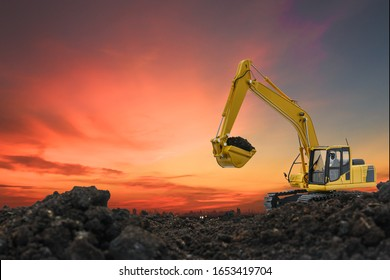 Excavators are digging the soil in the construction site on the orange  sky background