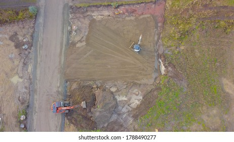 excavators doing the earthwork, groundwork while building a house, construction site, aerial view