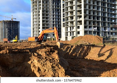 Excavators and dozers digs the ground for the foundation and construction of a new building.  Excavator load the sand to the heavy dump truck on construction site. Apartment renovation program