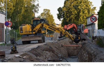 Excavators front digging holes in the street  - roadwork in industrial site and area in sunny and summer season - Kongsvinger, Norway (28th july 2019)
