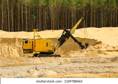 Excavators at  Sand Quarry Big  orange digger in open sand mine is waiting for new shift.