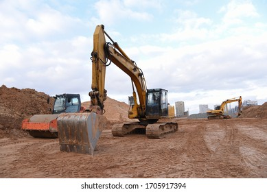 Excavators and soil compactor during road works at construction site. Backhoe digging the ground for the foundation and for laying sewer pipes district heating. Earth-moving heavy equipment