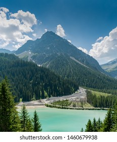 excavators and wheel loaders at the mouth of a mountain river in Arosa in the Swiss Alps move silt and rock sediment for construction use