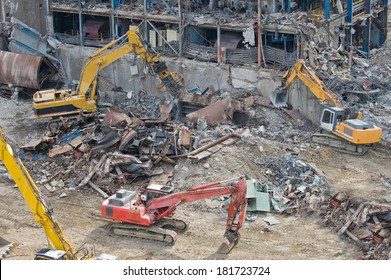 Excavators working in a demolition site in front of a  big metal construction destroyed