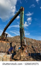 Excavators are working on mountain garbage or large piles of waste on a fresh blue day.
