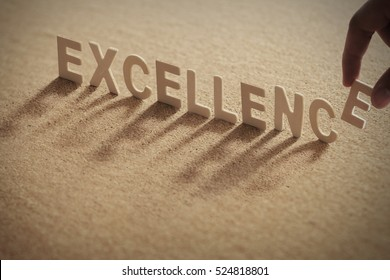 EXCELLENCE word on compressed board with human's finger at E letter