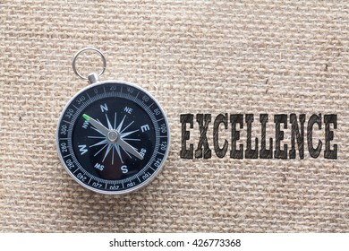 Excellence written on burlap background with compass,Conceptual