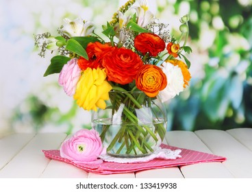 Excellent buttercup flowers in glass vase on wooden table on natural background
