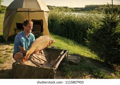 excellent catch. Fishing adventures, carp fishing. Mirror carp, freshwater fish. Fisherman with big carp