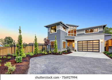 Excellent curb appeal of a Modern craftsman style home accented by landscaping, gray siding, large windows and Frosted Glass Garage Door. Northwest, USA