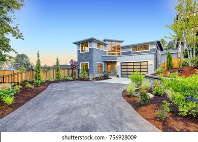 Excellent curb appeal of a Modern craftsman style home accented by landscaping, garage with glass door and long asphalt driveway. Northwest, USA
