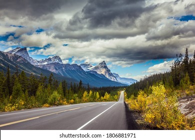 Excellent highway crosses the Rocky Mountains of Canada. Magnificent northern autumn. Yellow and orange leaves adorn the landscape. The concept of automotive, eco and photo tourism
