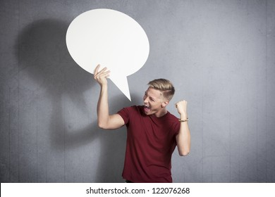 Excellent news: Overjoyed successful man holding white blank speech bubble with space for text isolated on grey background.