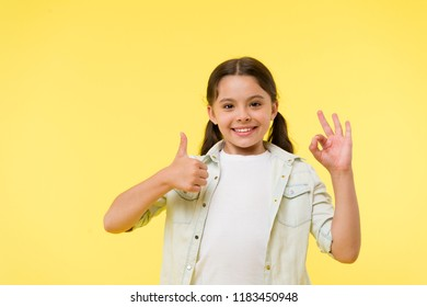 Excellent quality. Kid girl shows thumb up and ok gesture yellow background. Child highly recommend excellent quality. Girl happy smiling recommend high quality product. Sincere recommendation.