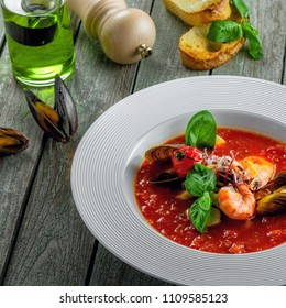 Excellent soup made of tomato and seafood on a rustic wooden table. Plate of healthy Italian meal.