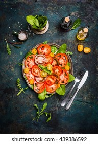Excellent various tomatoes salad with colorful tomatoes , cutlery  and salad dressing on dark rustic background, top view. Italian food