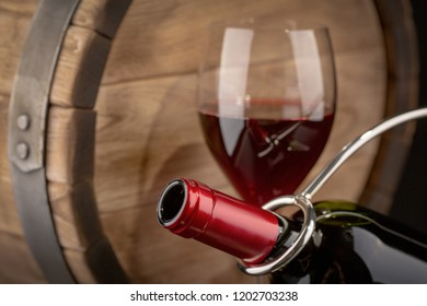 Excellent wine bottles, wine glass, barrel rustic wooden table: traditional winemaking and wine tasting concept